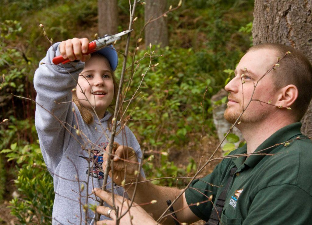 Child and staff member doing trail work.
