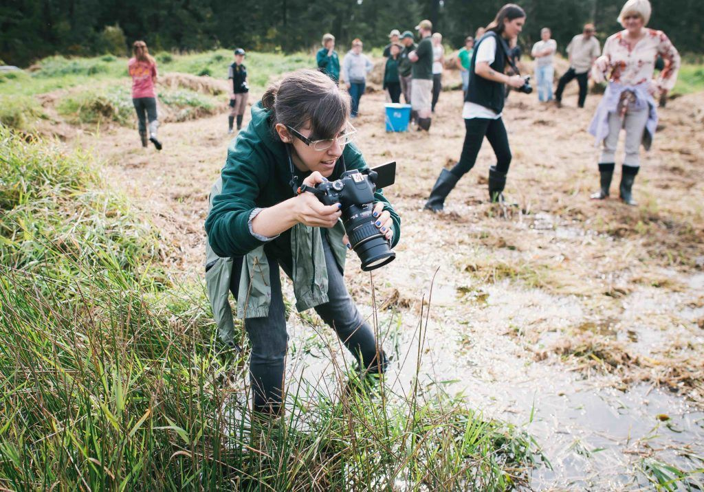 Woman in field with camera doing citizen science